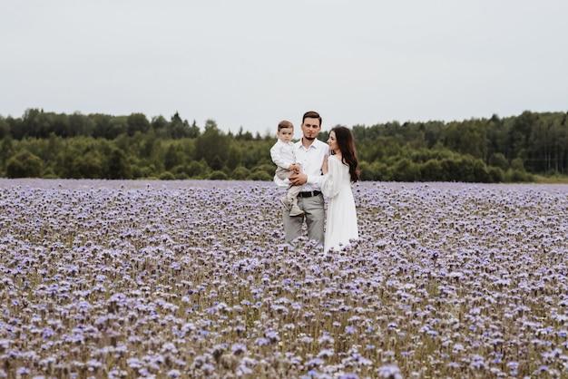 咲く紫色のフィールドの背景にママ、パパと息子