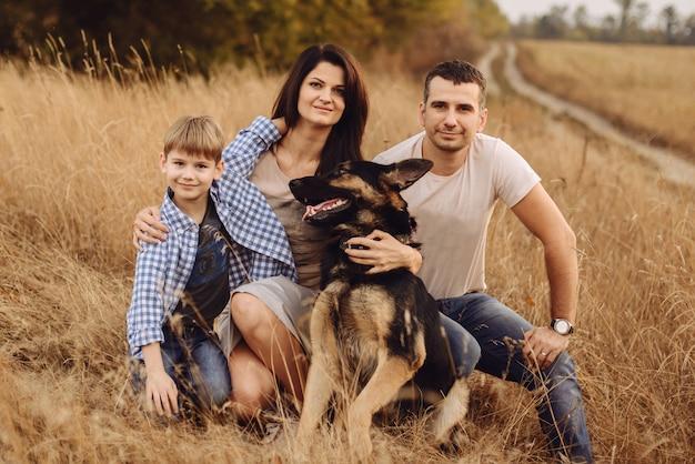 Мама папа и сын сидят на траве со своей собакой