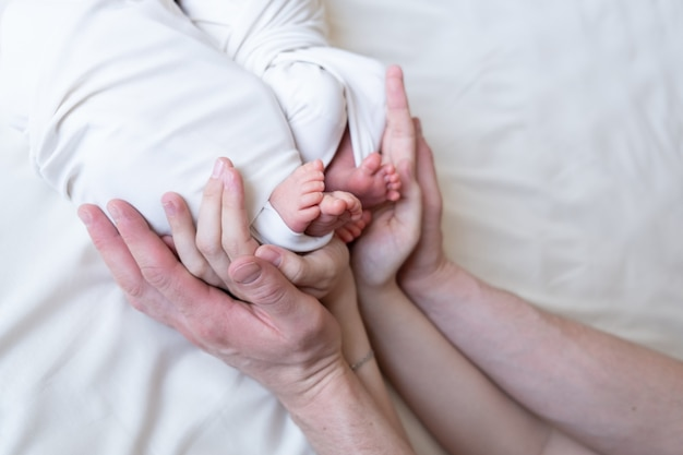 Mom and dad hands hold small legs of their two newborn twin babies