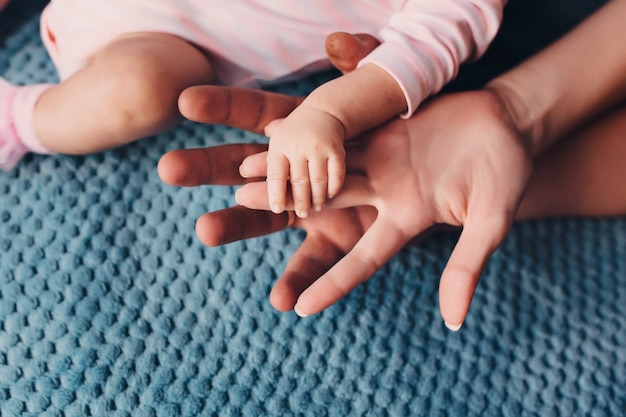 Mom and dad hold baby's hand. children's handle