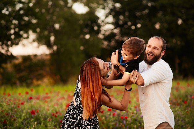 Mom and dad hold their little son on the arms standing on the green field with poppies