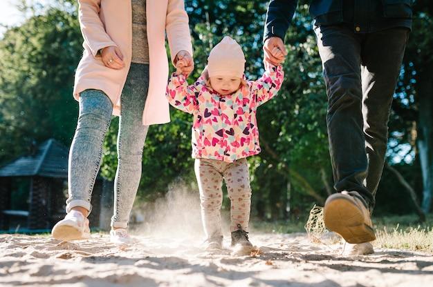 Мама, папа, держась за руки, дочь, бегая по песку на пляже. красивая счастливая молодая семья на прогулке в осеннем лесопарке. закройте вверх.