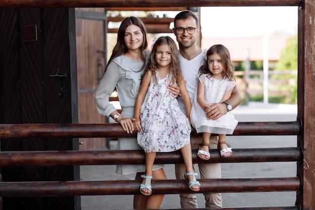 Мама, папа обнимают дочки с удовольствием сидят на природе и смотрят на природу. молодая семья проводит время вместе в отпуске, на открытом воздухе.