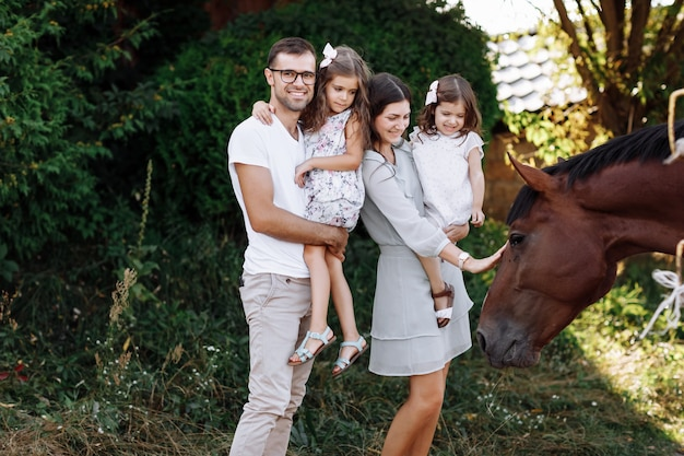 Мама, папа обнимают дочерей, с удовольствием гуляют по ферме и смотрят на лошадь. молодая семья проводит время вместе в отпуске, на открытом воздухе.