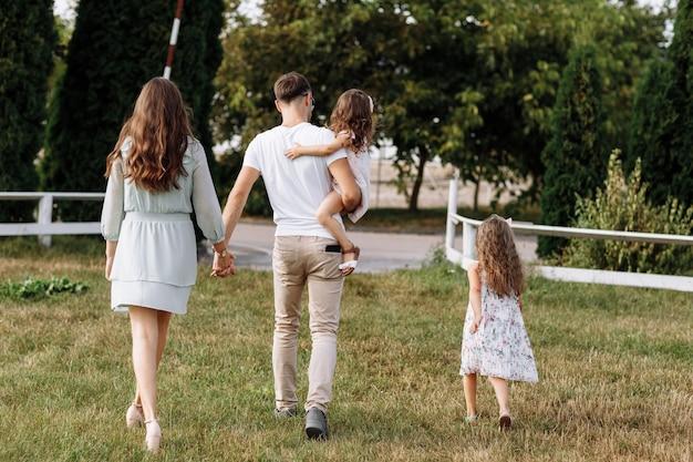 Мама, папа обнимают дочки с удовольствием гуляют на природе и смотрят на природу. молодая семья проводит время вместе в отпуске, на открытом воздухе.