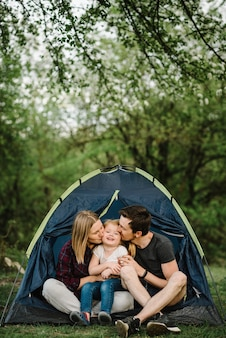 Mom, dad kisses and hugs a kid and enjoying a camping holiday in the countryside