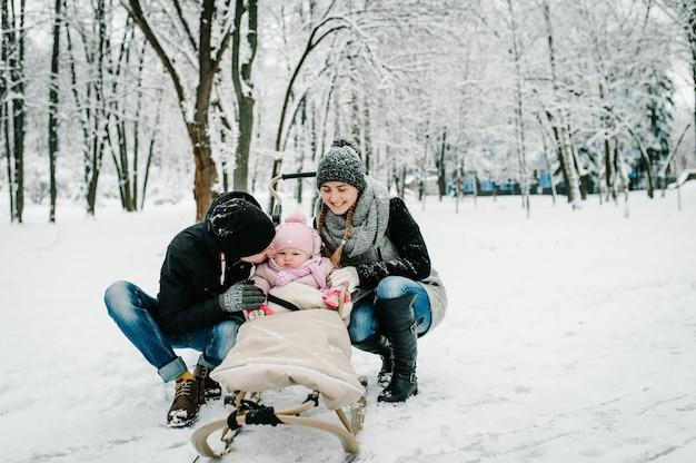 ママ、パパのキス娘は冬に屋外に立っています。
