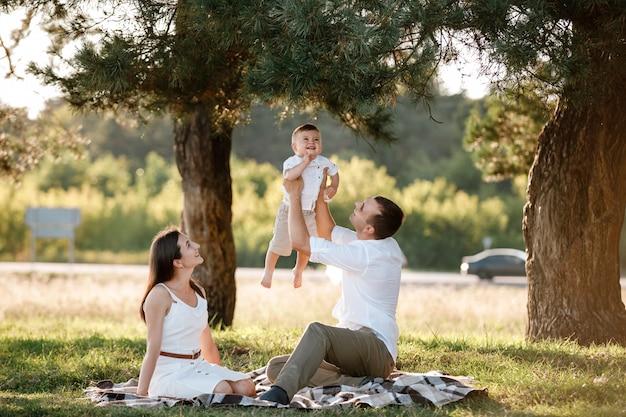 お母さん、お父さんは男の子を空中で高く持ち上げ、彼女の笑顔を見ます。夏の日に公園で息子と遊んで時間を過ごす幸せな親。セレクティブフォーカス。