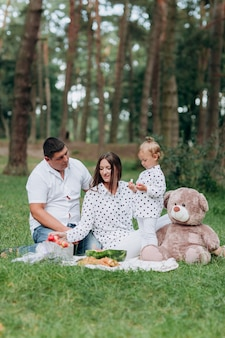 Mom, dad and little daughter on the picnic with teddy bear in the park outdoors. the concept of summer holiday. mother's, father's, baby's day. family spending time together on nature. family look