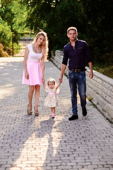 Mom, dad and little daughter walk in the park. happy family.