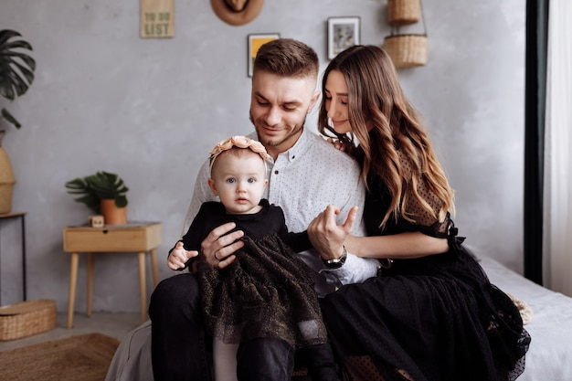 Mom, dad and little woman having fun and hugging at home on bed. mother's, father's and baby's day. happy family holiday indoors. family look. happy young family spending time together