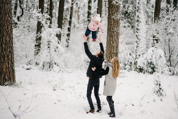 Мама, папа играет и подбрасывает дочку в зимнем лесопарке.