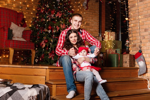 Mom and dad pose with their charming little daughter in decorated christmas studio. new year photo session.