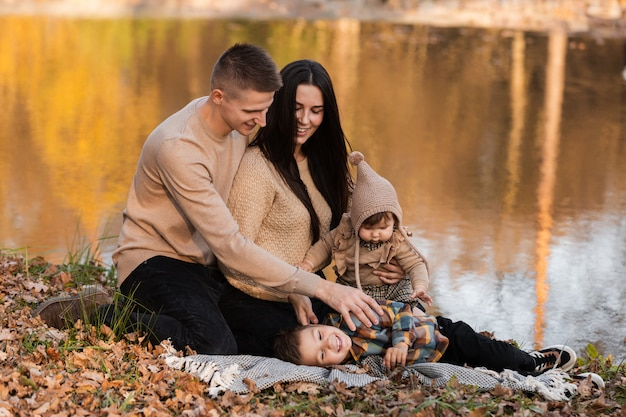 Мама папа сын и дочь возле озера в осеннем парке концепция семейного отдыха