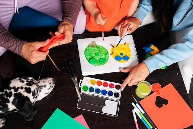 엄마, 아빠, 아들과 그들의 개가 집에서 플라스틱과 페인트를 가지고 노는
