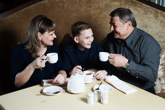 Mom, dad, son drink tea