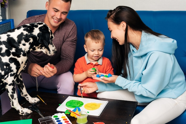 Mom, dad, son and their dog play with plasticine and paint at home