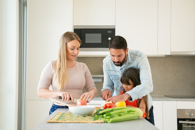 Mom and dad teaching kid to cook. young couple and their girl cutting fresh fruit and vegs for salad at kitchen table. healthy nutrition or lifestyle concept