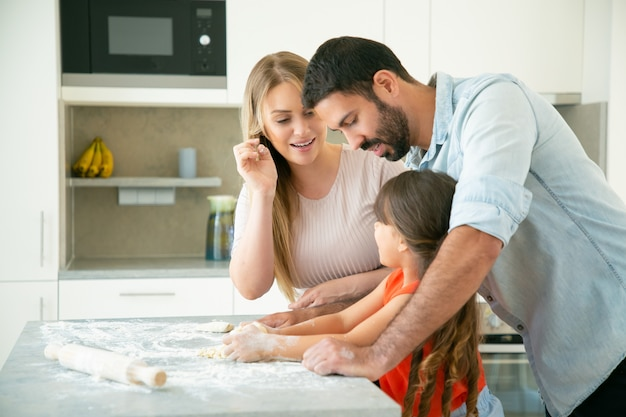 Mom and dad teaching kid to knead dough on kitchen table with flour messy. young couple and their girl baking buns or pies together. family cooking concept