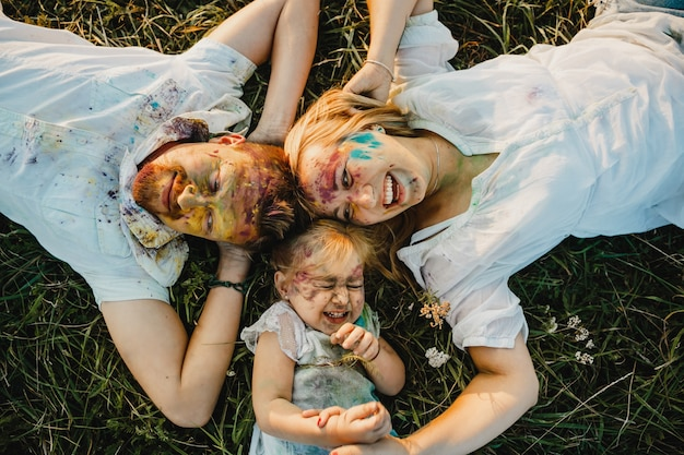 Mom, dad and their daughter covered with colorful paints lie on the green lawn