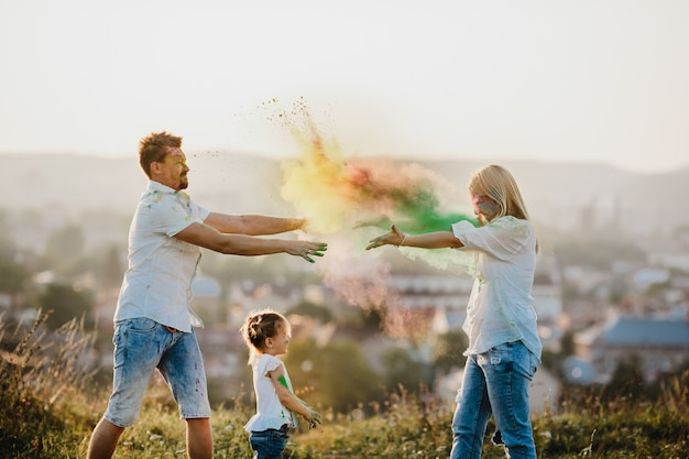 Mom and dad and their little daughter play with colorful smoke on the lawn