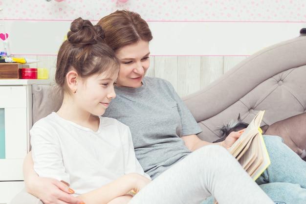 ママ、娘、犬がソファに座って本を読んでいます。幸せな家族の概念。