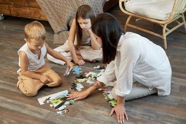 ママの娘と息子がパズルを床に置いた。家族向けの娯楽。女性の女の子と男の子が一緒に遊ぶ