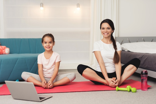 Mom and daughter are doing gymnastics on the mat at home.