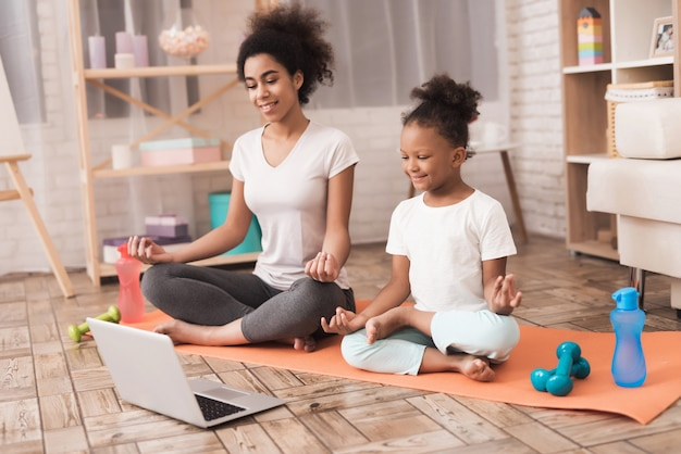 Mom and daughter are doing yoga at home.