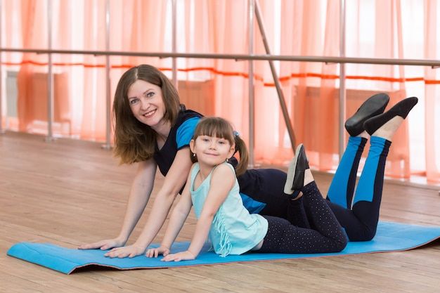 Mom and daughter are engaged in gymnastics.