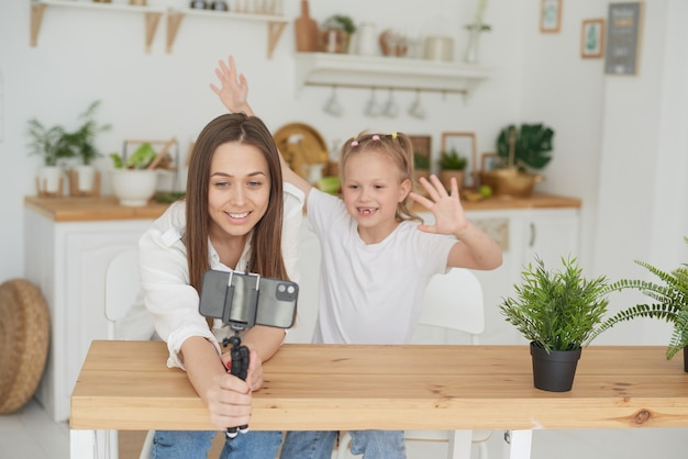 Mom and daughter are having fun and fooling around while recording a video blog. lifestyle. spending time with your family.