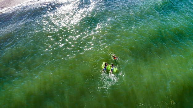 Mom and daughter are having fun in surf waves on the sea. happy moments with children.
