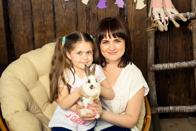 Mom and daughter are holding a cute fluffy white rabbit. easter celebrations.
