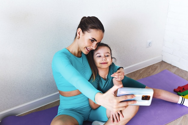 Mom and daughter are photographed on the phone during fitness classes at home