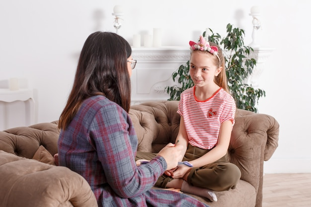 Mom and daughter are sitting on the couch and chatting. girl teenager with emotions tells her mother a story. daughter shares her feelings with her parent. leisure mothers and daughters