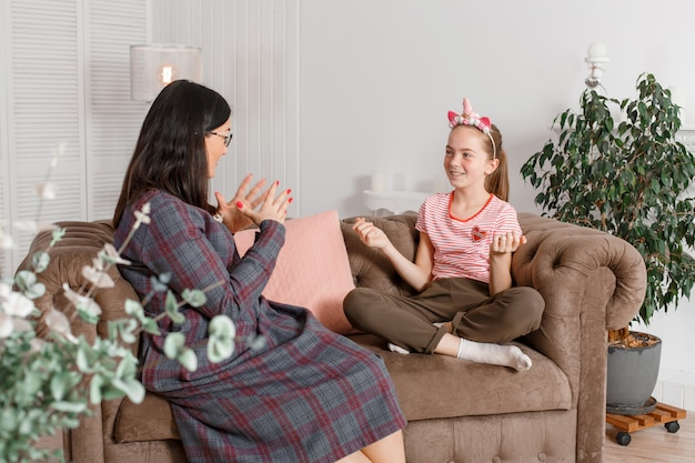 Mom and daughter are sitting on the couch and chatting