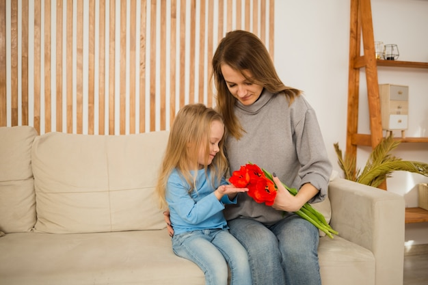 Mom and daughter are sitting on the couch and looking bouquet of red tulips in the room