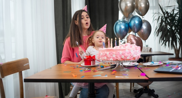 Mom and daughter are sitting at the festive table and blowing out the candles on the cake together.