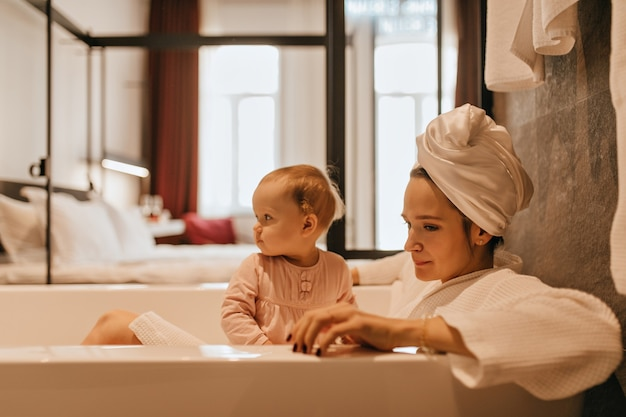 Mom and daughter are sitting in snow-white bath. woman in towel on her head is holding baby.