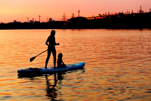 Mom and daughter are surfing on a paddle board at sunset