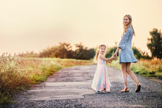 Mom and daughter are walking along country road