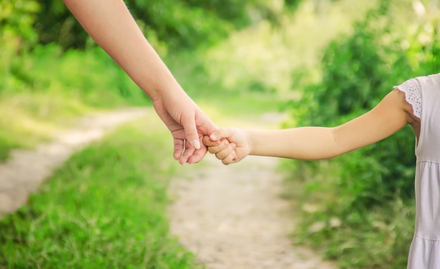 Mom and daughter are walking along the road holding hands.