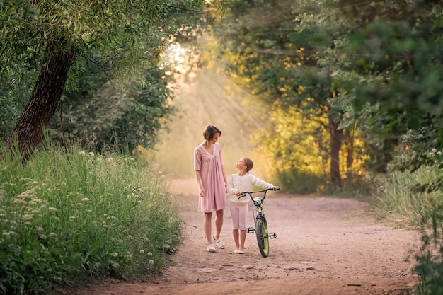Mom and daughter are walking in a park with a bicycle
