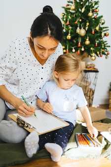 Mom and daughter are writing a letter to santa claus on the wall of a christmas tree and gifts young woman teaches little cute girl to draw a new year card family cozy moments