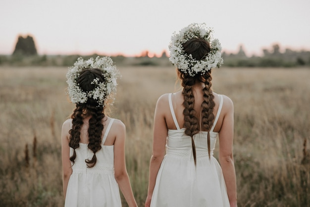 Mom and daughter backs in white dresses with braids and floral wreaths in boho style in summer