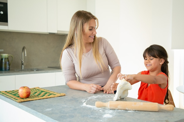 Mom and daughter baking together and making dough at kitchen counter. medium shot. family cooking concept
