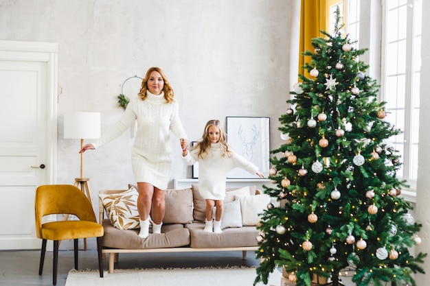 Mom daughter blonde hair dressed light sweaters, waiting holiday, room decorated celebrate christmas, jumping sofa, fun children's games