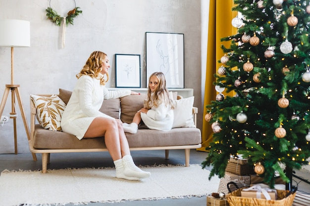 Mom daughter blonde hair dressed light sweaters, waiting for the holiday, room decorated celebrate christmas, sitting on the couch