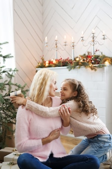 Mom and daughter in christmas-decorated living room