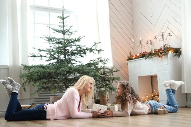 Mamma e figlia in soggiorno decorato di natale